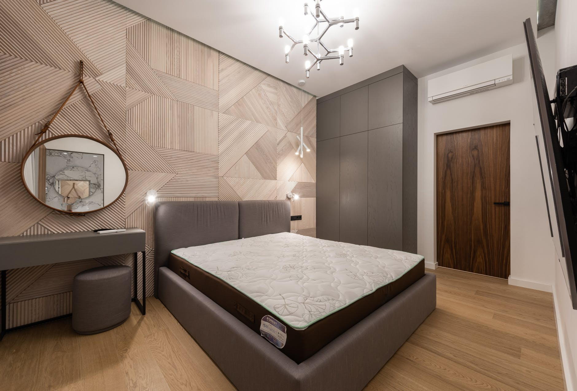 bedroom interior with bed near table with pouf under mirror